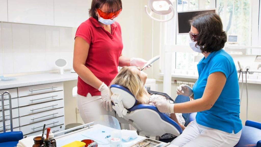 Patient Receiving Dental Curing Ultraviolet Light Inside Mobile Dental Unit