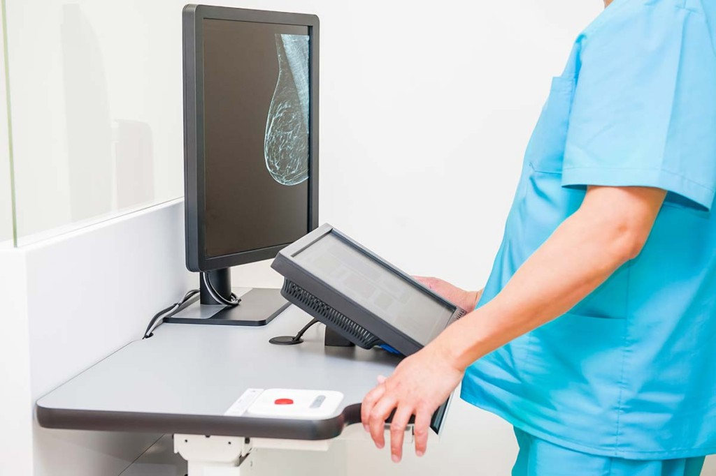 Doctor Looking At Mammogram Inside Womens Health Clinic