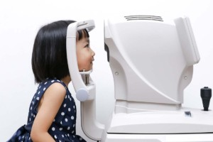 Asian Girl Doing Eyes Examination Through Auto Refraktometer Inside Mobile Ophthalmology Clinic
